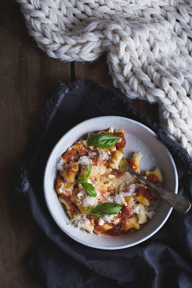 Roast garlic and onion tomato sauce with ricotta gnocchi, parmesan, basil and salt and pepper in a bowl