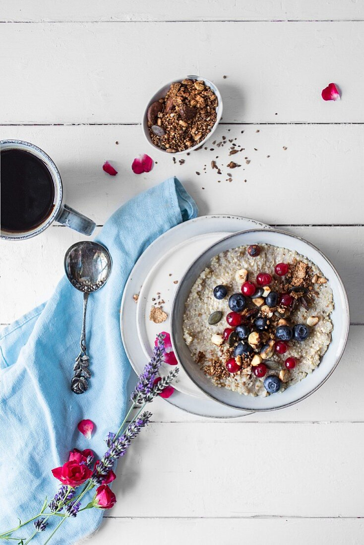 Quinoa porridge with fresh berries and cup of coffee
