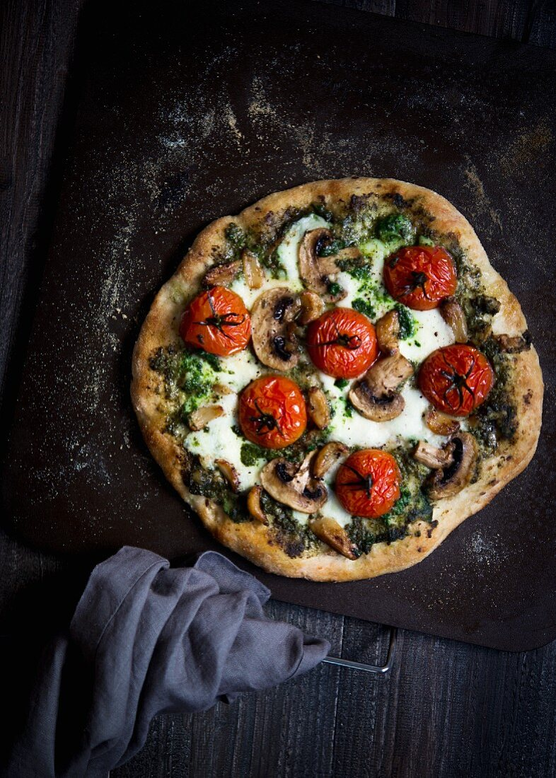 A vegetarian pizza with tomatoes, mushrooms, pesto and mozzarella