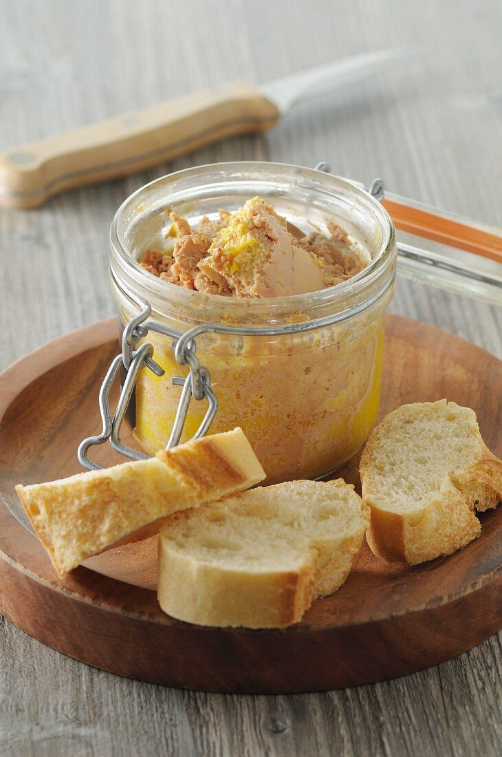 Foie gras in a glass jar with baguette slices