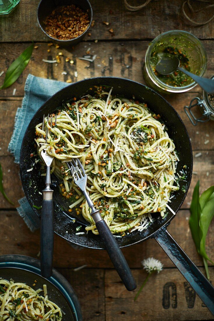 Wild garlic pesto spaghetti in pan with pamesan