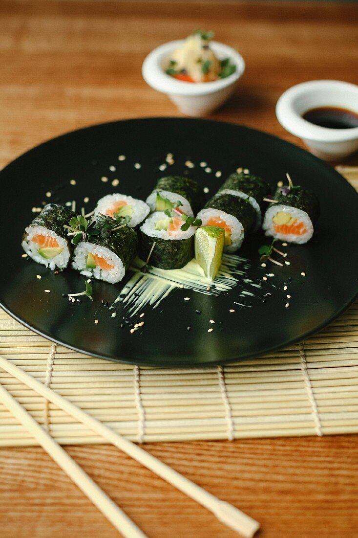 Maki Sushi with salmon and avocado on a black plate