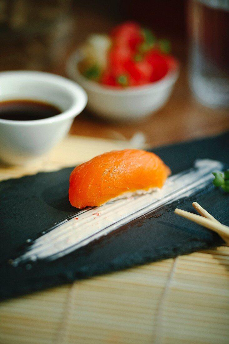 Nigiri sushi with salmon on a black plate