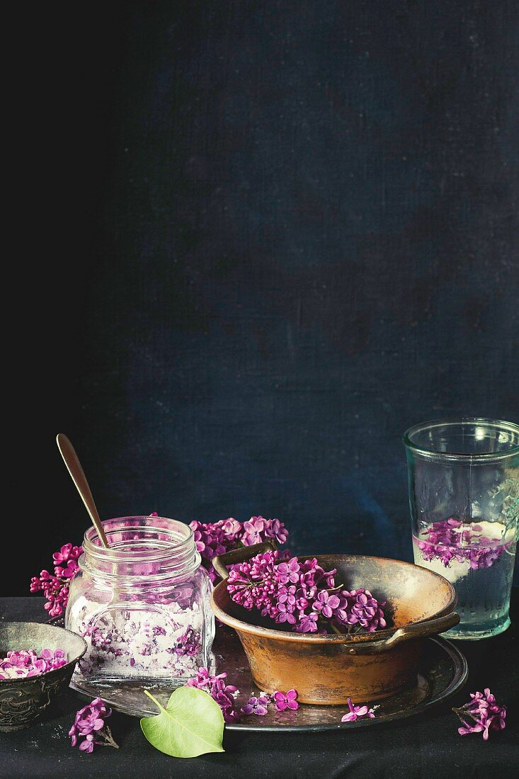 Glass jar of lilac flowers in sugar, glass of lilac water with lemon and fresh lilac flowers in vintage copper bowl