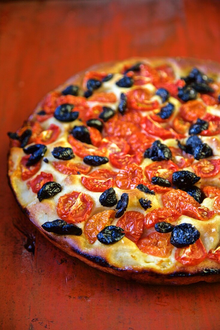 Focaccia with Tomatoes and Olives on a red table (Italy)