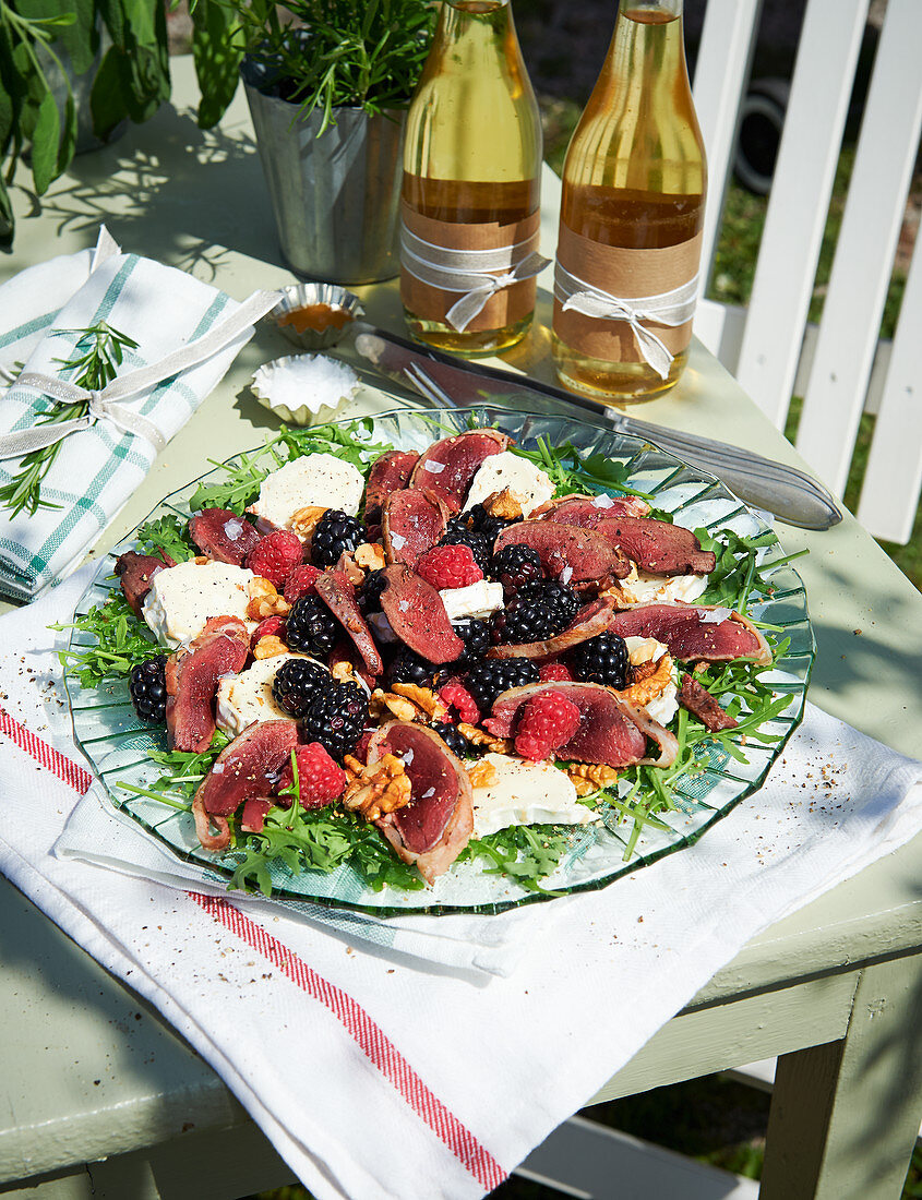 A summer salad with grilled duck breast wrapped in bacon