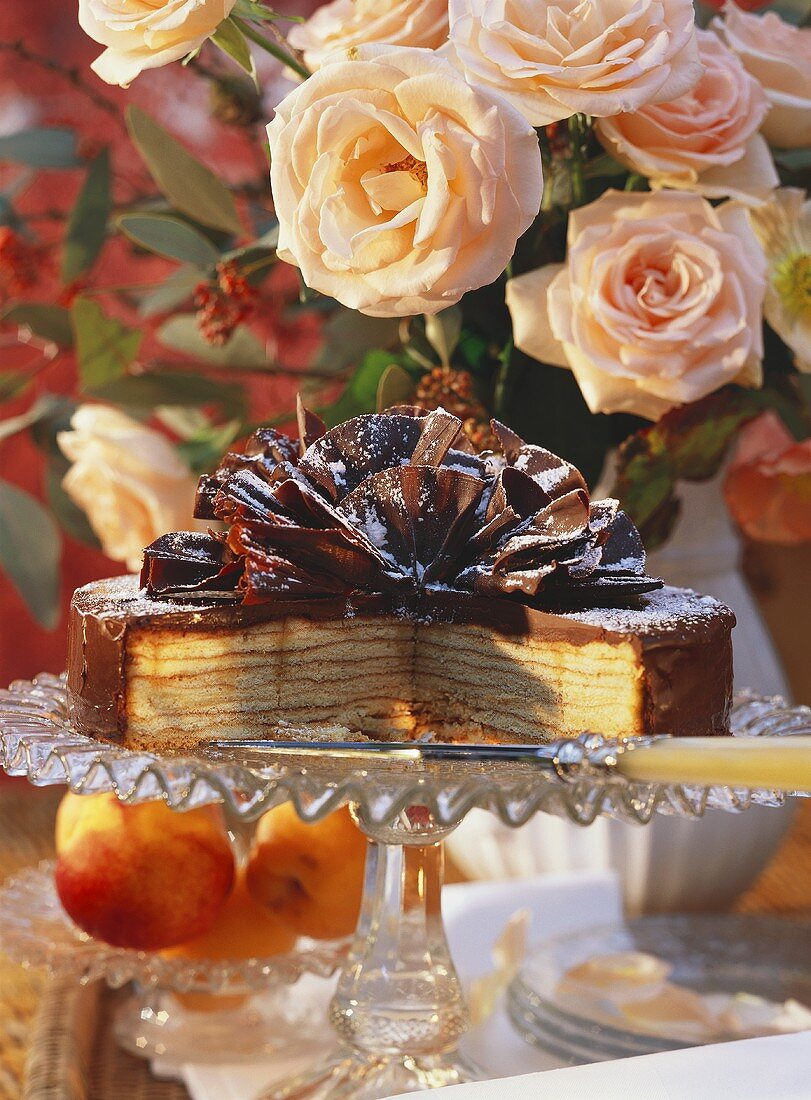 Tree cake gateau decorated with chocolate fans, a piece cut