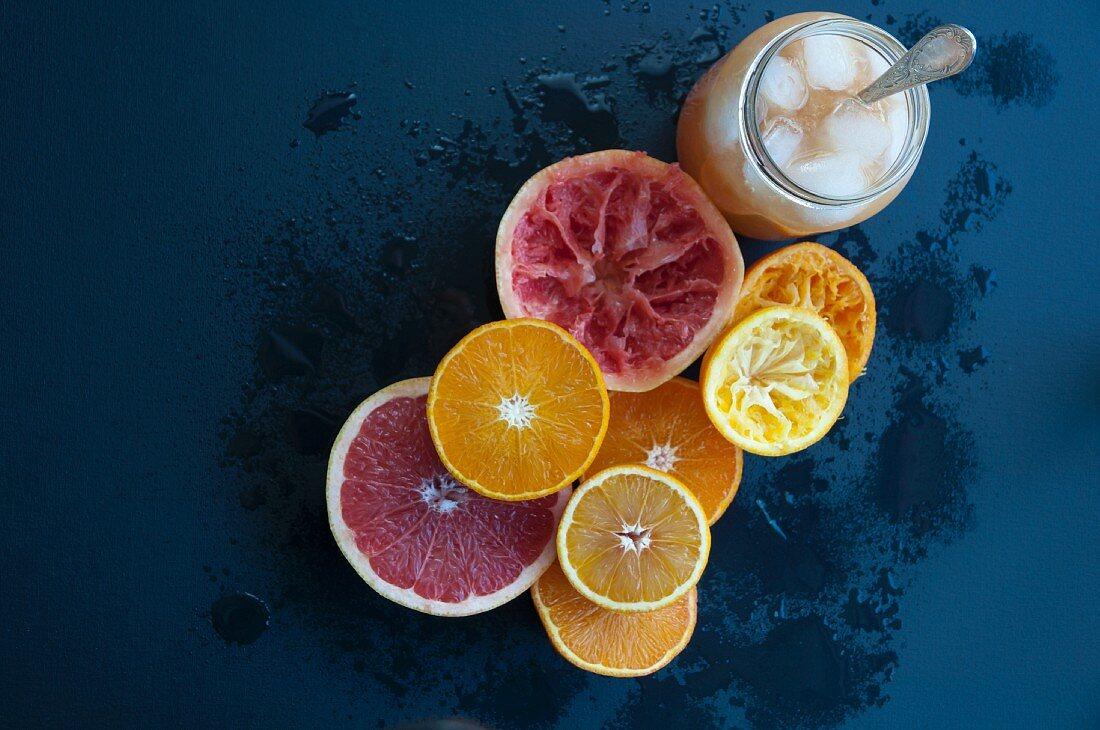 Zitrusfrüchte, teilweise ausgepresst, daneben ein Glas Saft mit Eiswürfeln