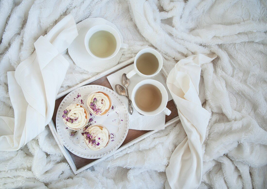 Vanilla cupcakes with tea on a tray on a cosy white blanket (seen from above)