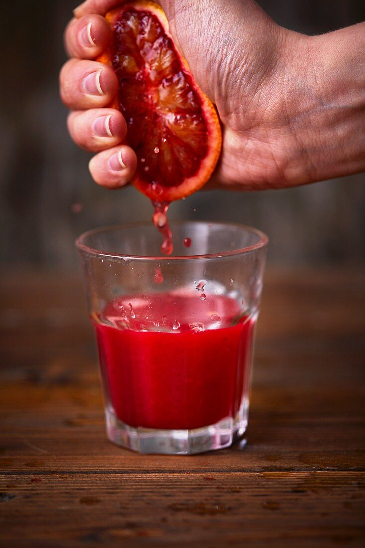 Blood orange being squeezed out by hand over a glass