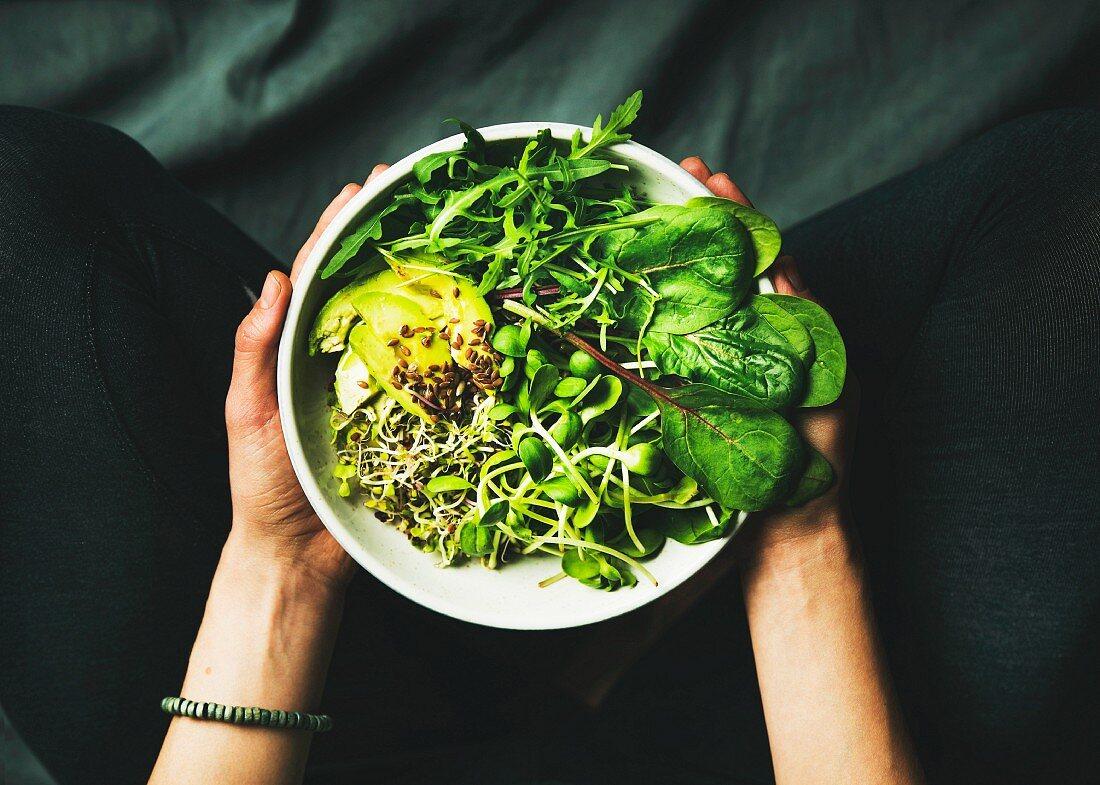 Vegane grüne Power-Bowl mit Spinat, Rucola, Avocado, Samen und Sprossen