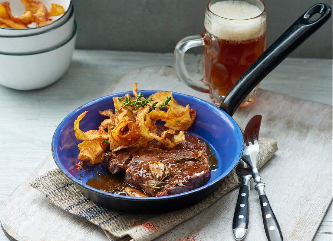 Entrecote steak with potato crisps and a glass of dark beer