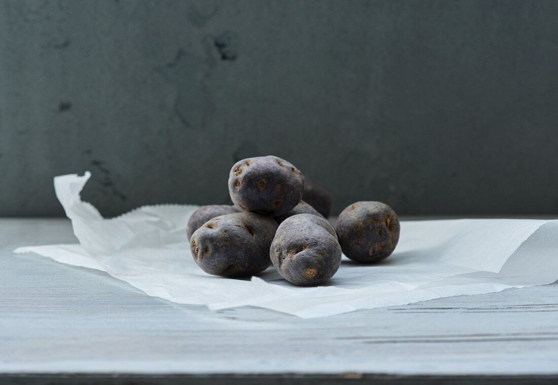 Several violet potatoes on a piece of paper