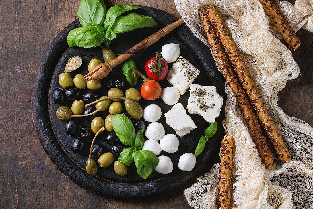 Mediterranean appetizer antipasti board with green black olives, feta cheese, mozzarella, capers, pepper, basil with grissini bread sticks