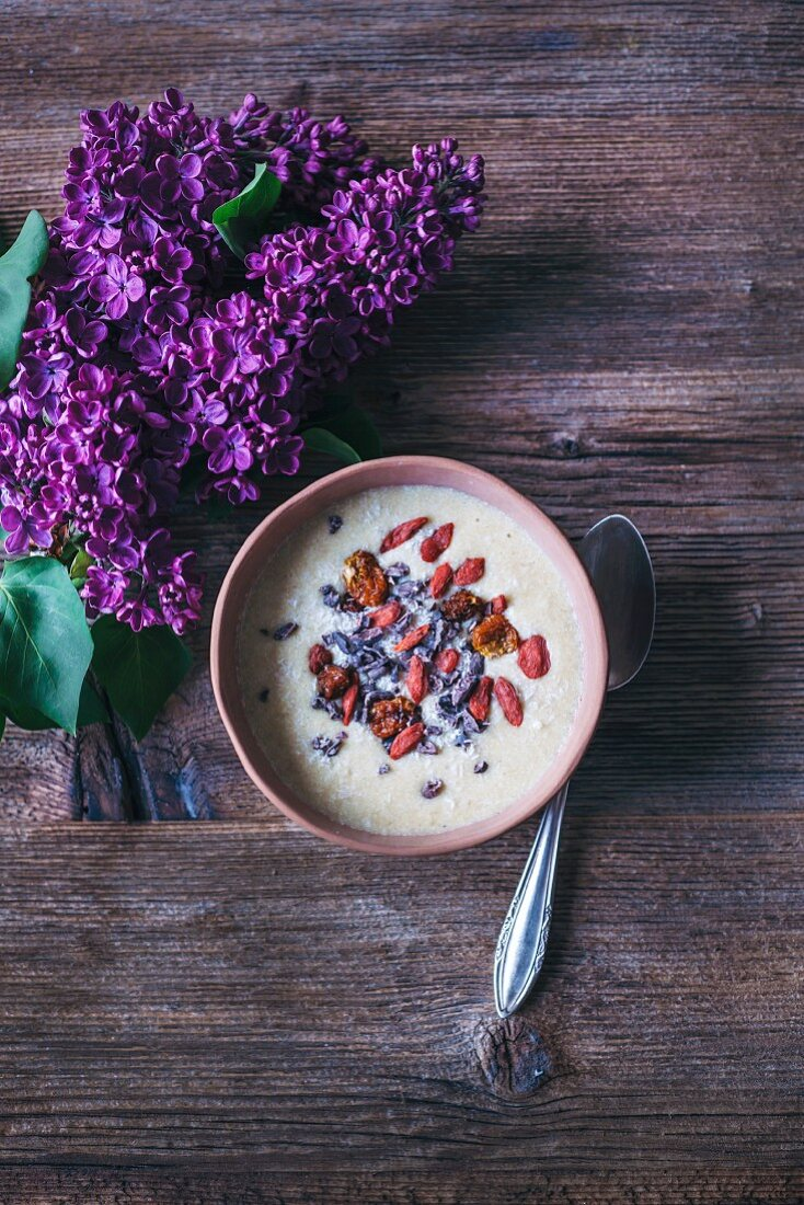 Banana coconut smoothie bowl toppwd with coconut, cacao nibs, goji berries and inka berries