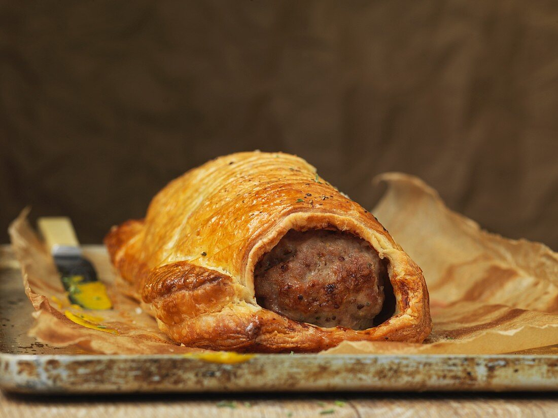 Homemade sausage patties with puff pastry on baking sheet