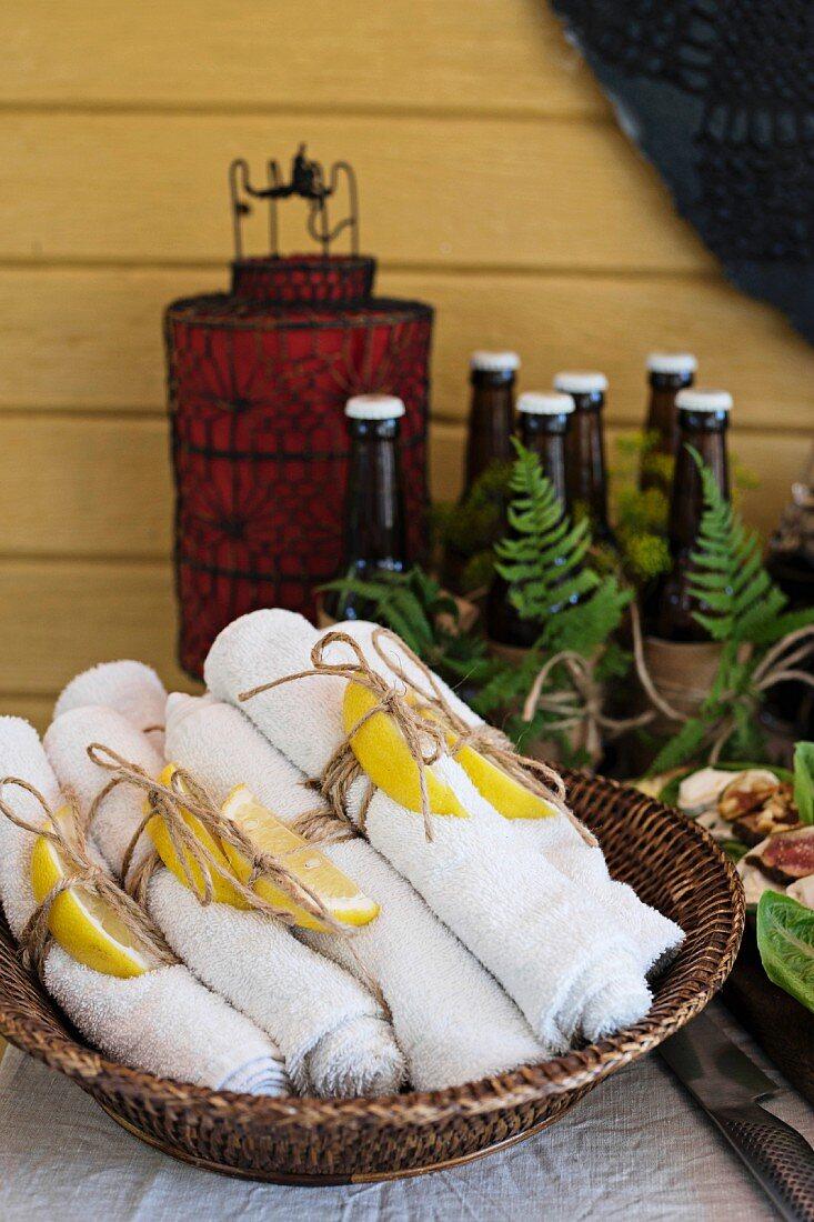 Rolled towels with lemon slices in wicker basket on dresser