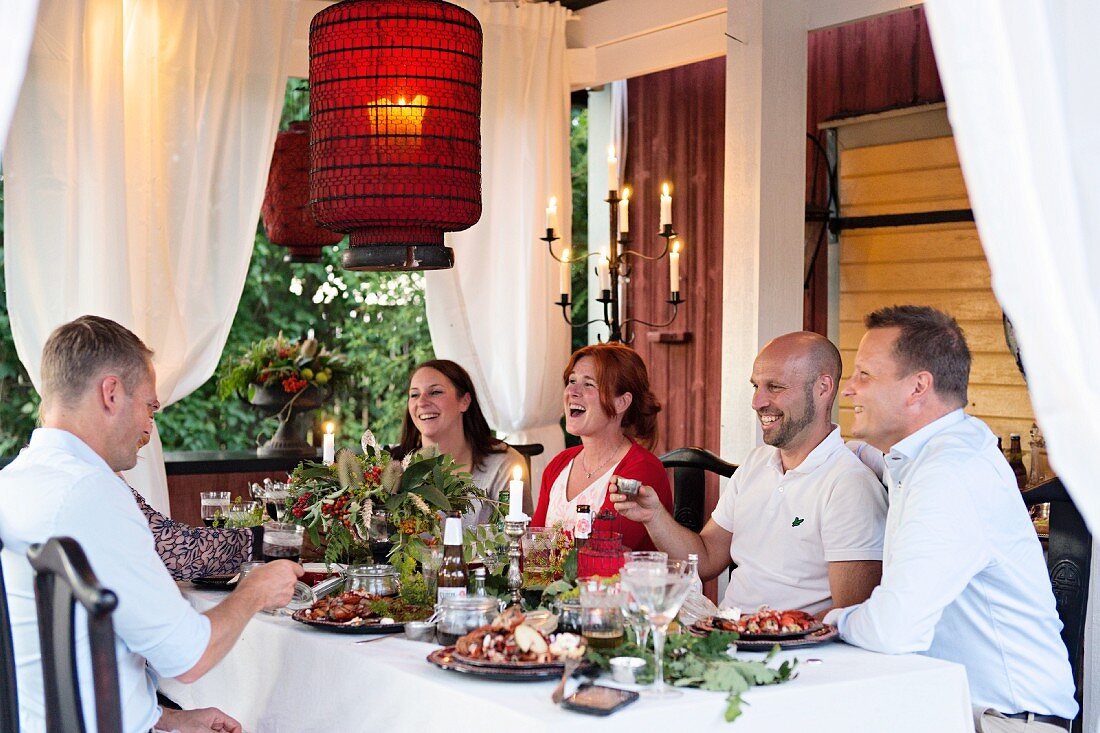 A garden party on a pavilion lit with red lanterns