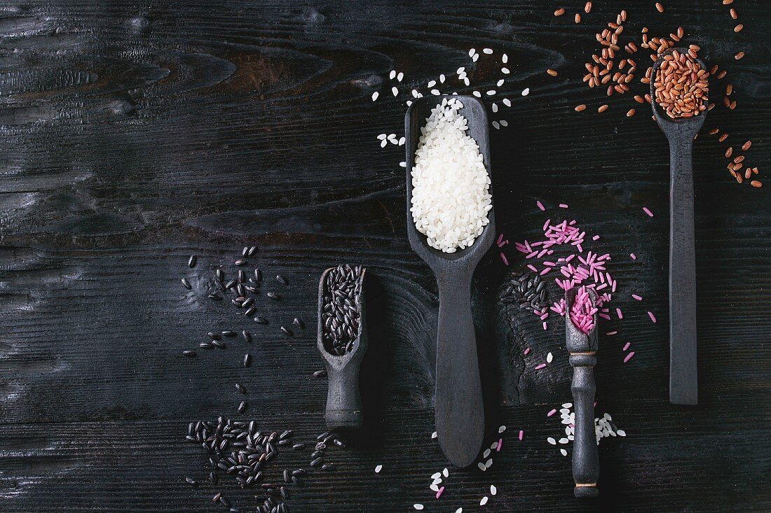 Variety assortment of raw uncooked colorful rice white, black, brown, pink in black spoons and scoop over wooden background