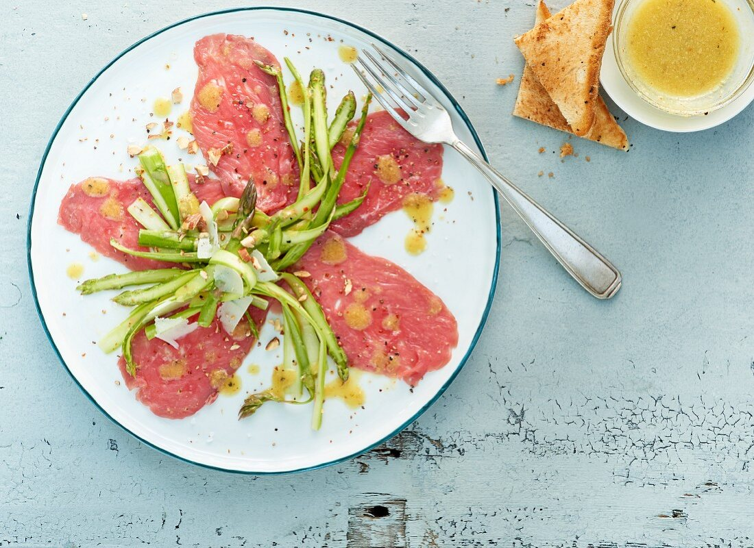 Beef carpaccio with green asparagus strips and toasted bread