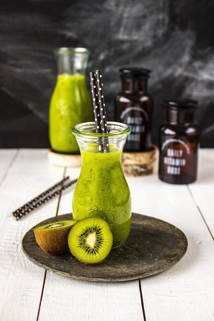 A green smoothie in a small carafe with drinking straws