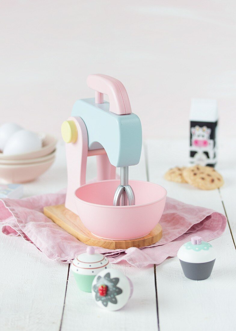 A child's mixer in pastel colors on a wooden surface