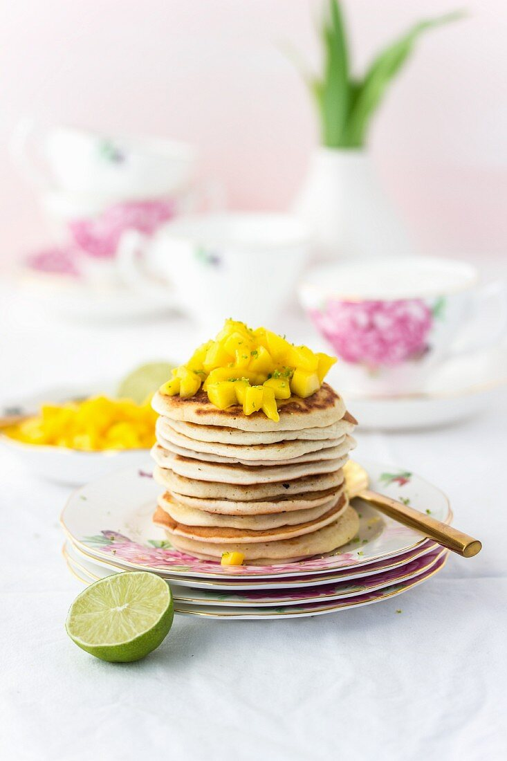 A pile of small pancakes and mango cubes