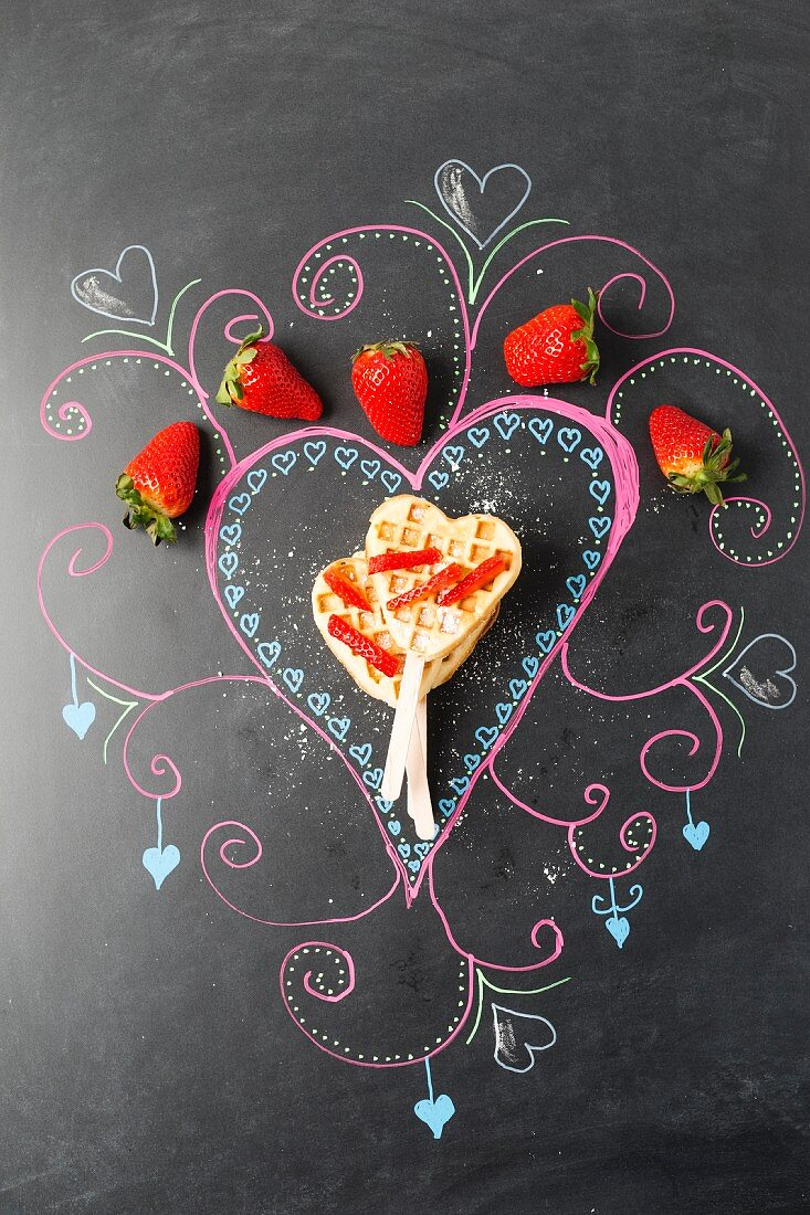 Waffles with sticks and strawberries on a decorated blackboard