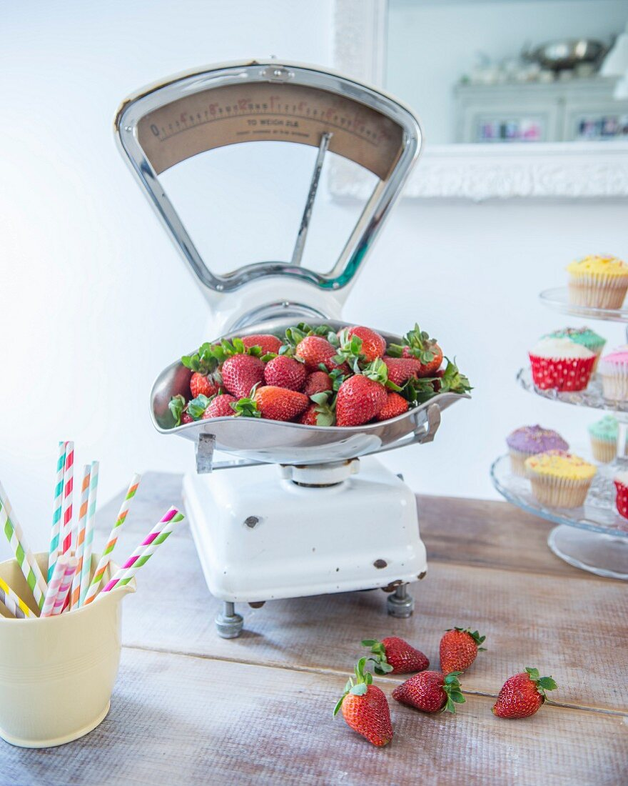 Strawberries on retro kitchen scales and rustic wooden table