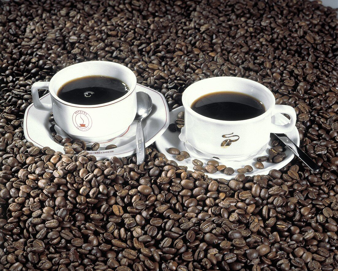 Two Cups of Coffee Surrounded By Coffee Beans