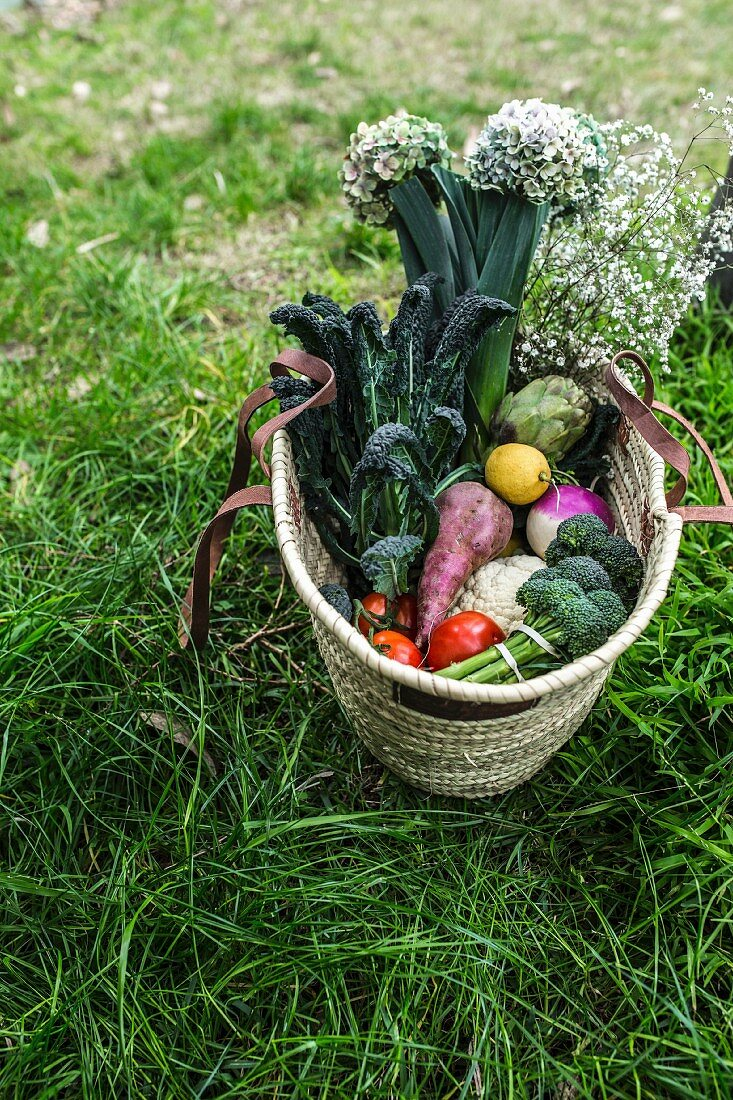 A shopping basket with vegetables, fruit and flowers