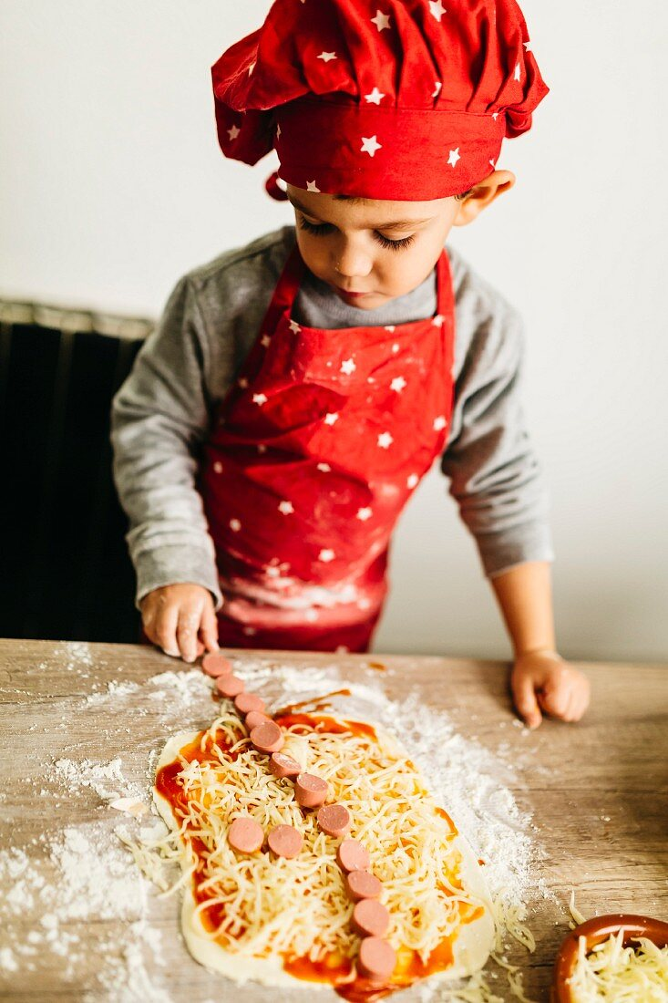 Little boy preparing pizzas at home, dressed like a cheff
