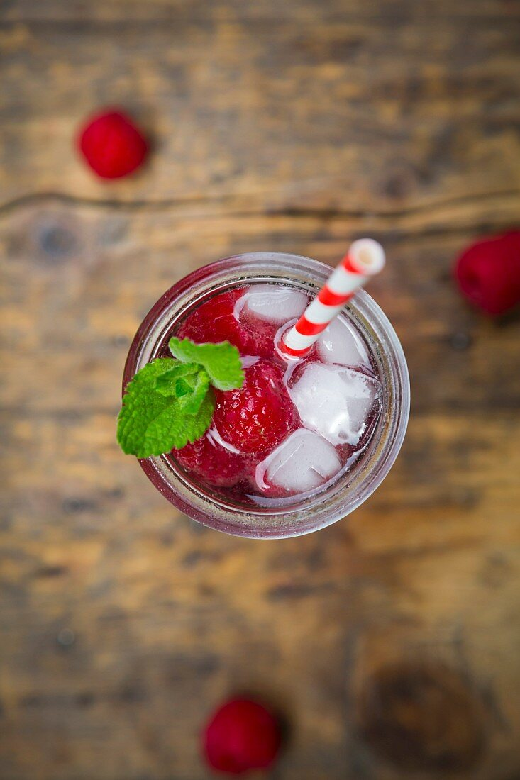 Raspberry champagne in glass, drinking straw, mint and raspberries