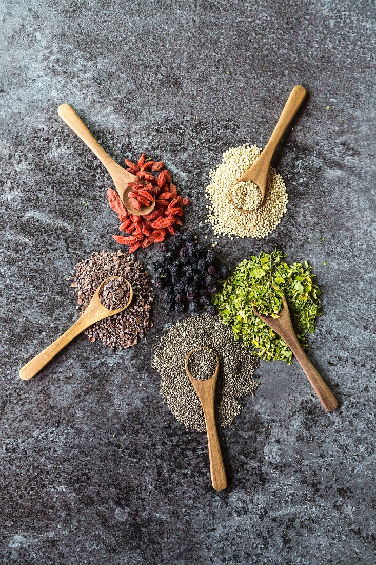 Wooden spoons of chokeberries, chia, aronia, quinoa, moringa and wolfberries