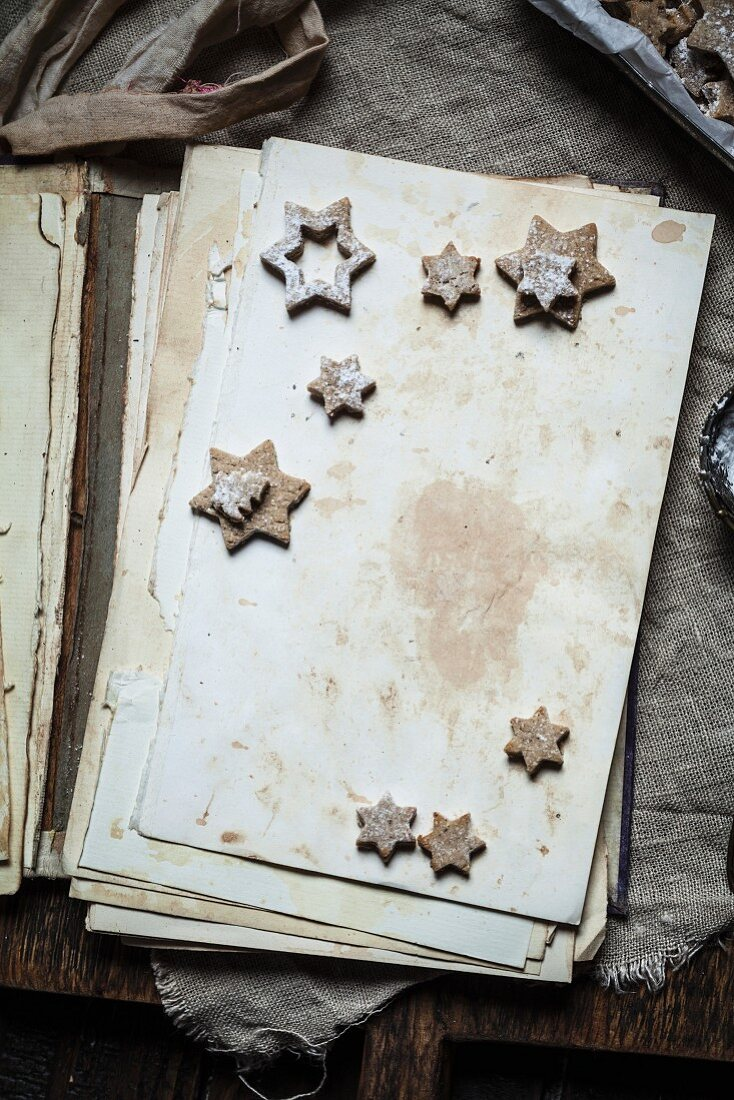Home-baked Christmas cookies with powdered sugar on old book