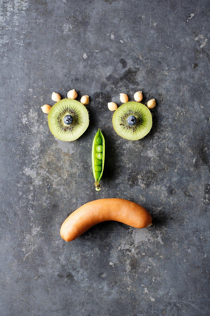 A photo to symbolise hidden carbohydrates - a sad smiley made up of fruit, vegetables and a sausage