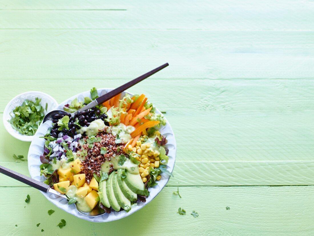 Brightly coloured quinoa and veggie bowl with avocado, mango and black beans