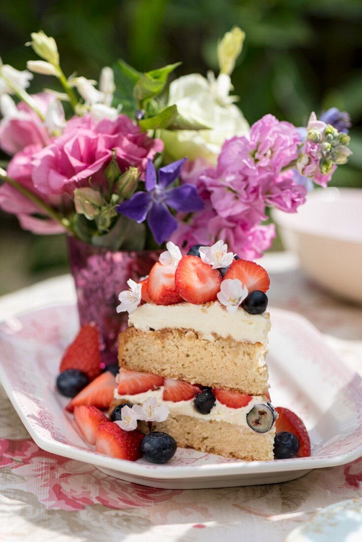 A piece of Victoria Sponge cake with berries on a table outdoors