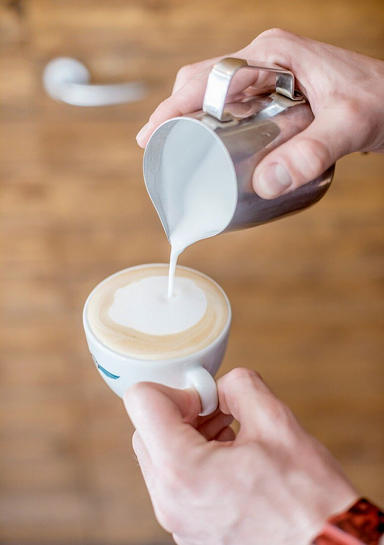 A barista pouring frothed milk into a cappuccino cup