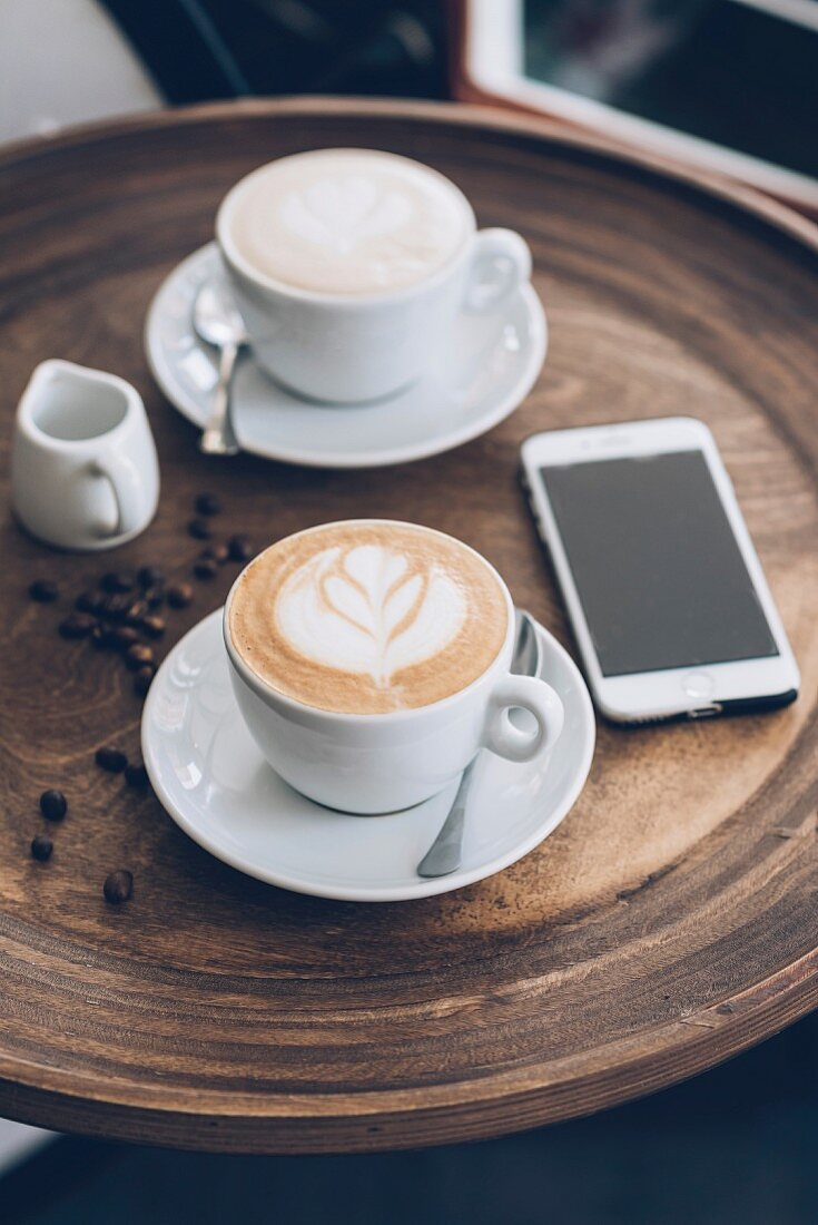Two cups of cappuccino next to a smartphone on a table in a café