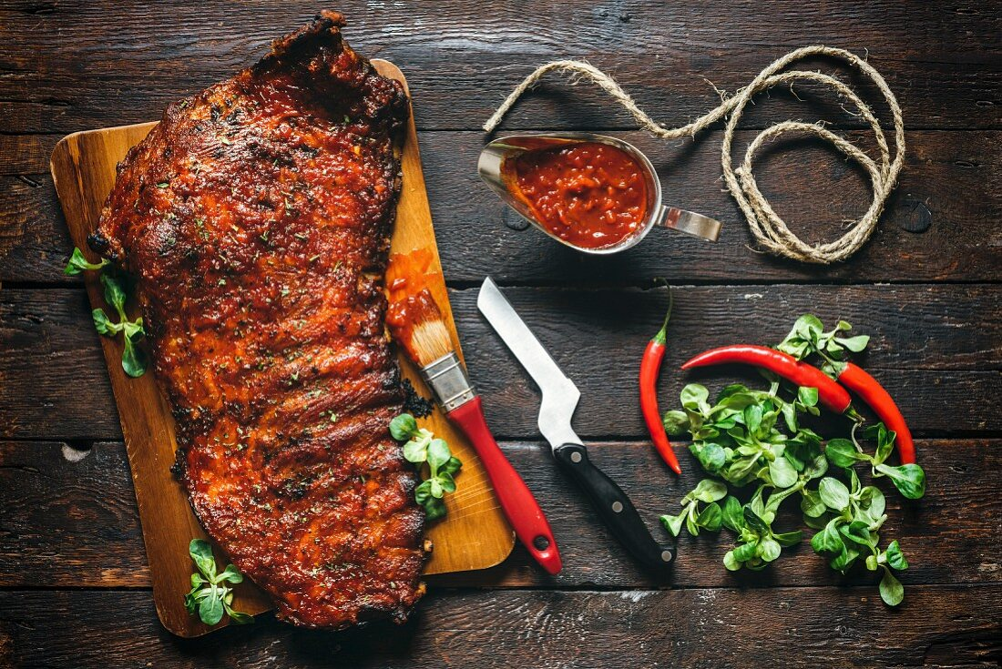 Served beef ribs with bbq sauce on wooden background