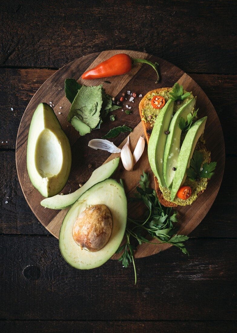 Sandwich with avocado and pesto sauce on wooden board