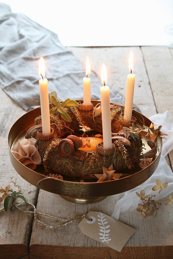 A traditional advent wreath on a golden stand with a hand painted label on a rustic table