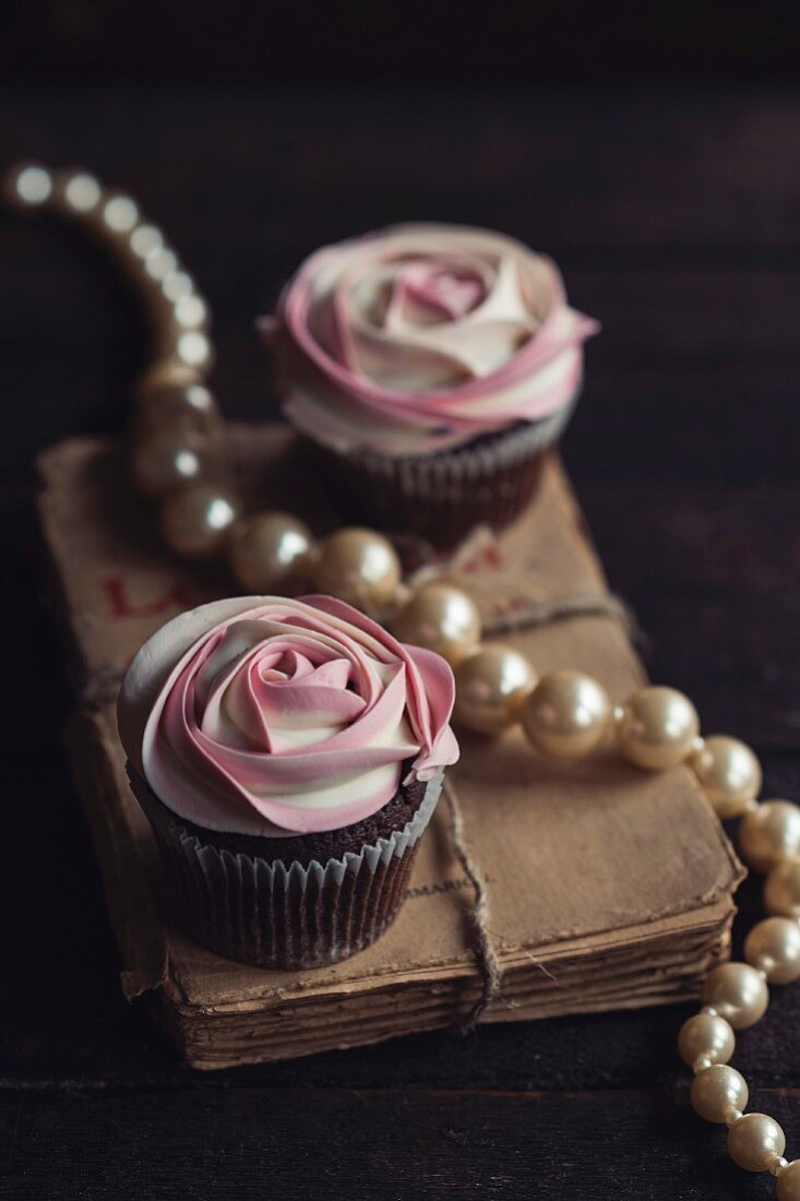 White rosese cupcakes served on wooden background