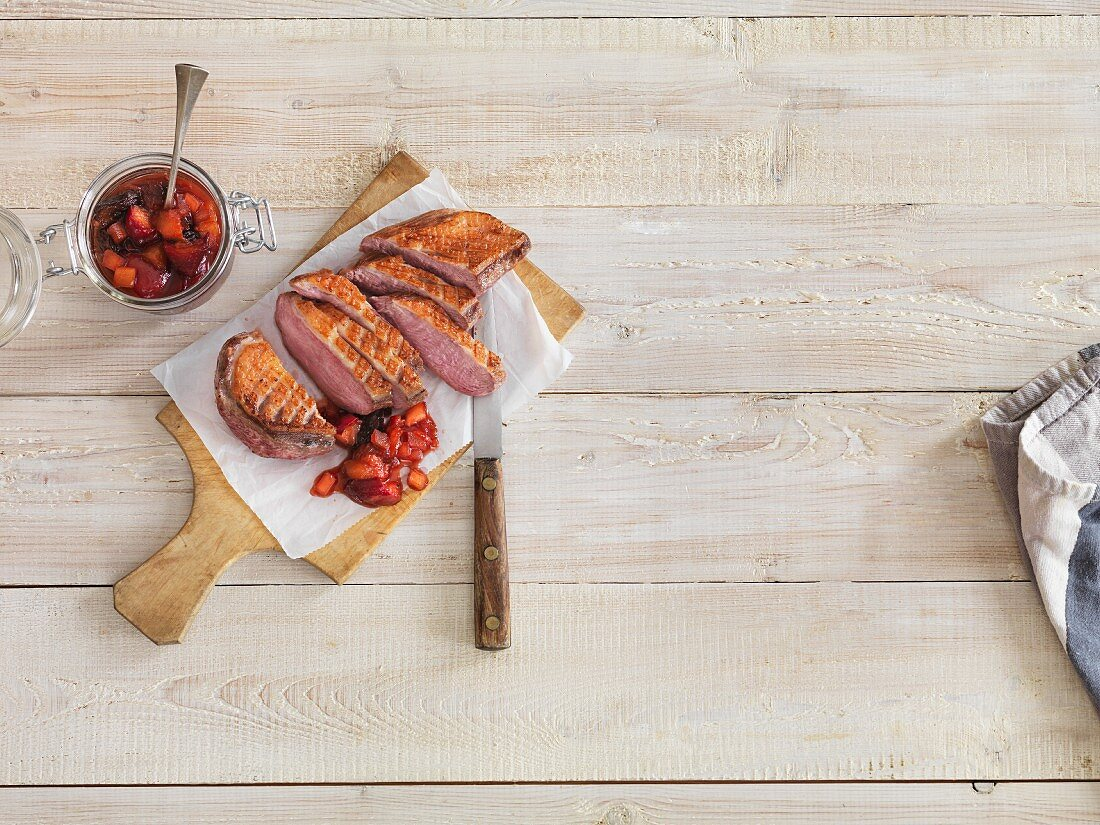 Grilled duck breast with chutney on a wooden board