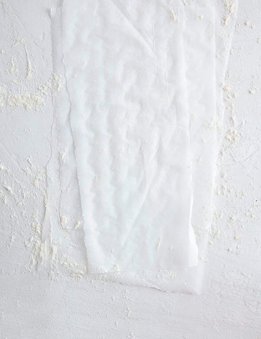 Baking paper on a white background, dusted with flour