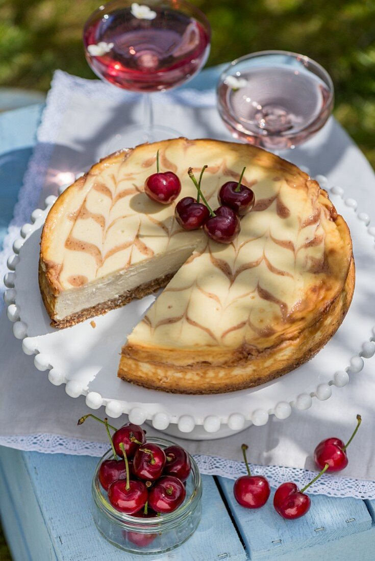 Honey cheesecake with cherries on a table outdoors