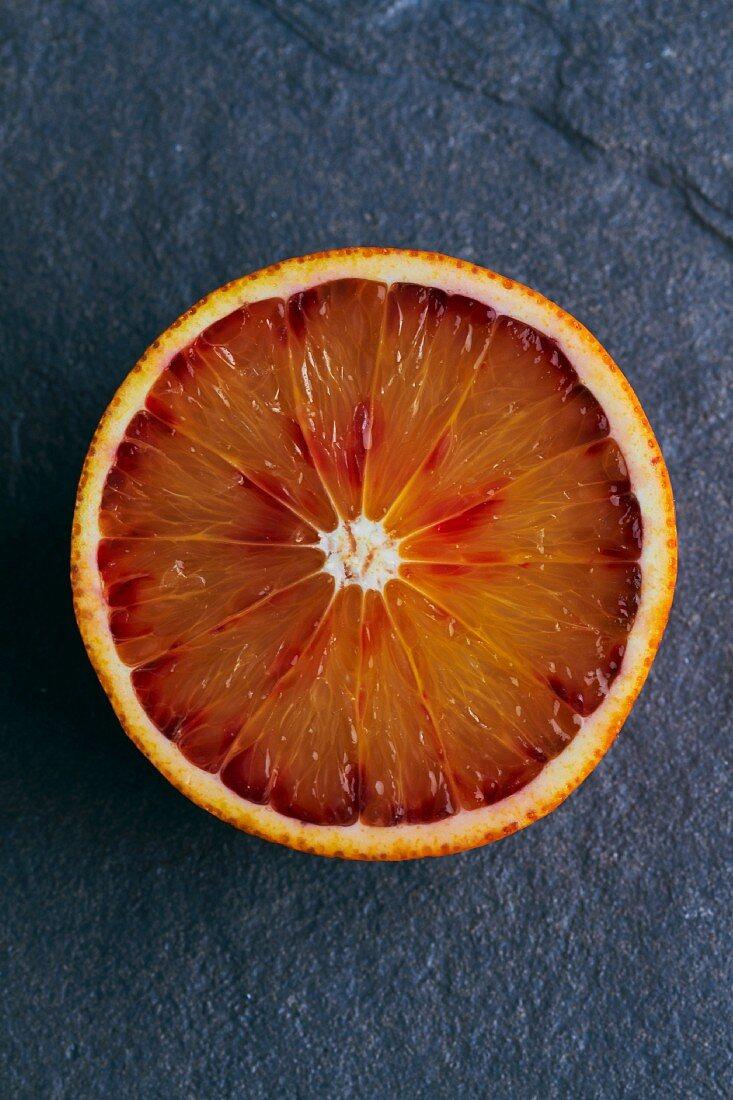 Half a blood orange on a grey background