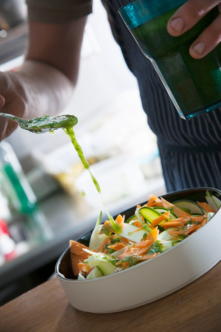 A vegetable salad is drizzled with dressing