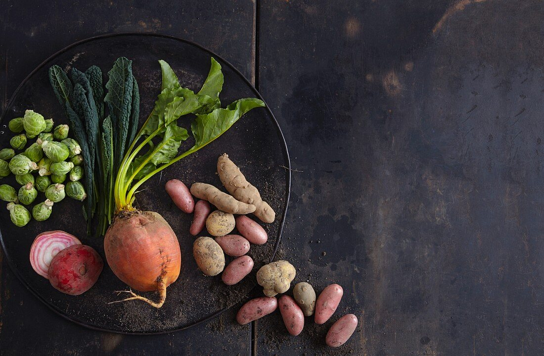 A vegetable still life (potatoes, beetroot, green cabbage, brussels sprouts)